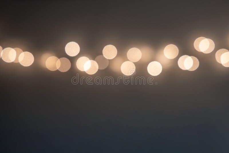 Línea de luces doradas borrosas en fondo beige suave fotos de archivo libres de regalías