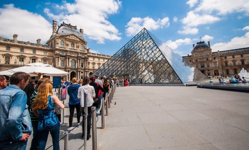 Línea de muchos turistas en la fuente del museo del Louvre fotografía de archivo