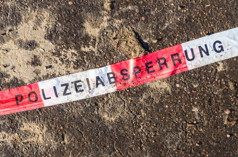 Línea de policía alemana cinta blanca roja en la suciedad del asfalto de la calle fotos de archivo libres de regalías
