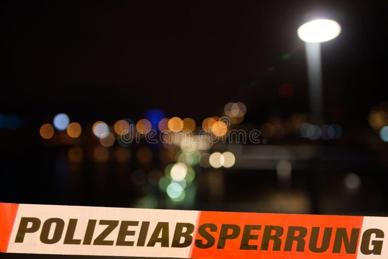 Línea de policía delante de luces de la ciudad por noche fotografía de archivo