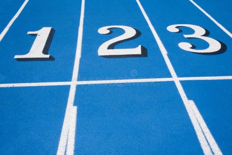 Línea de salida azul de la pista de raza una dos tres fotografía de archivo