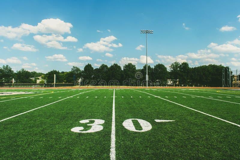 Línea de yardas 30 en campo de fútbol americano y el cielo azul imagenes de archivo
