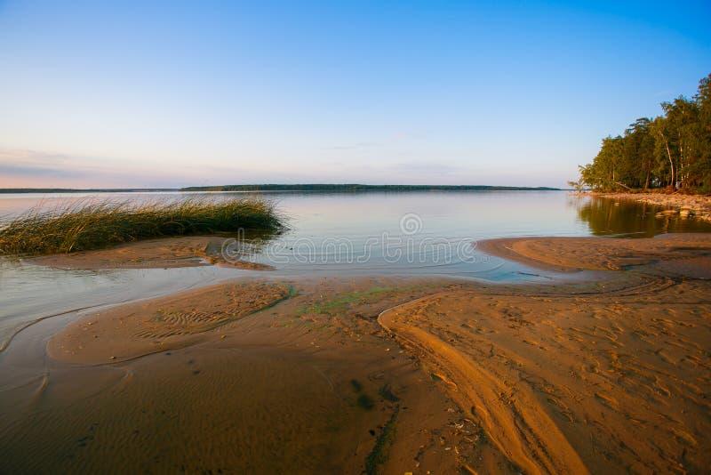 Línea del lago encendida con paisaje de descoloramiento de la luz del sol fotografía de archivo libre de regalías