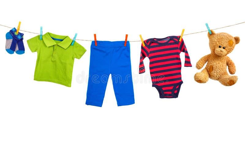 Línea del lavadero con ropa colorida en un fondo blanco imagenes de archivo