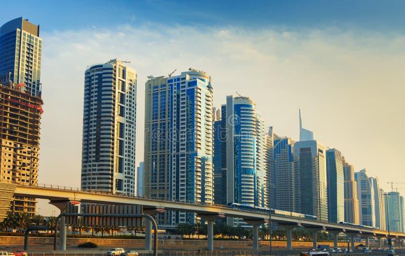 Línea del metro que pasa a través del puerto deportivo de Dubai con los rascacielos modernos alrededor, Dubai, United Arab Emirat foto de archivo libre de regalías