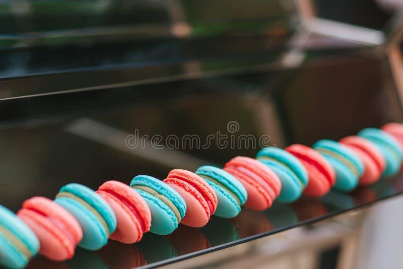 Línea diagonal del rosa y de los macarrones azules en el estante de cristal Conceptos m?nimos Galletas de almendra delicadas Espa imagenes de archivo