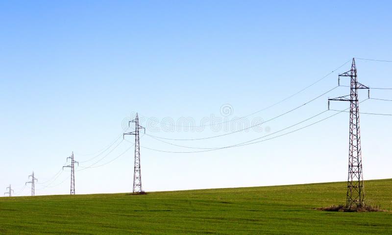 Línea eléctrica en campo verde imagenes de archivo