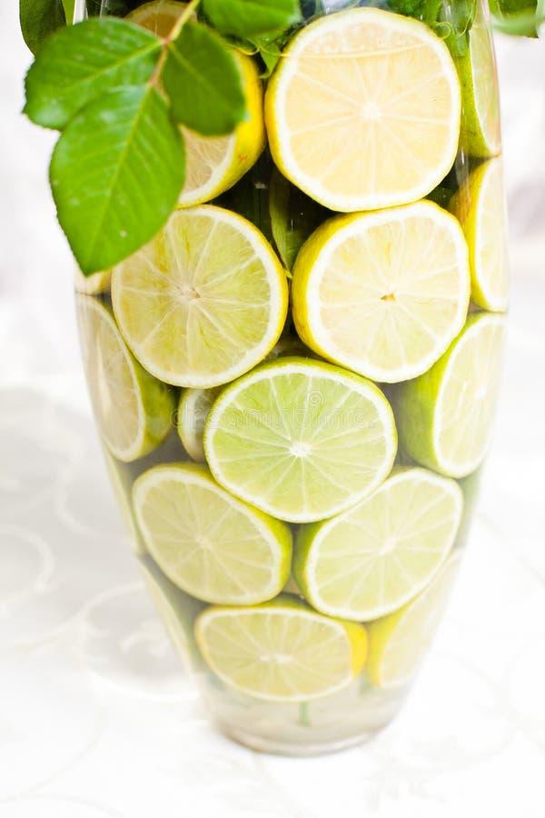 Línea florero de cristal con las rebanadas de limones. foto de archivo