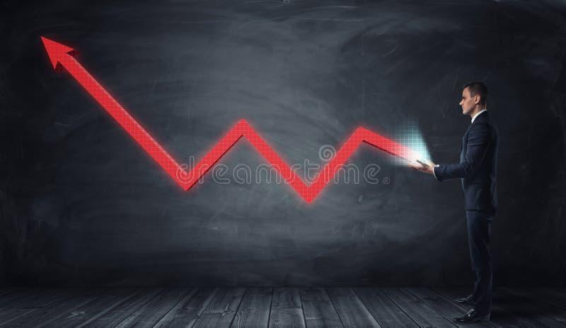 Línea gráfico roja enorme con una flecha vuelta hacia arriba que crece de las manos de un hombre de negocios fotografía de archivo