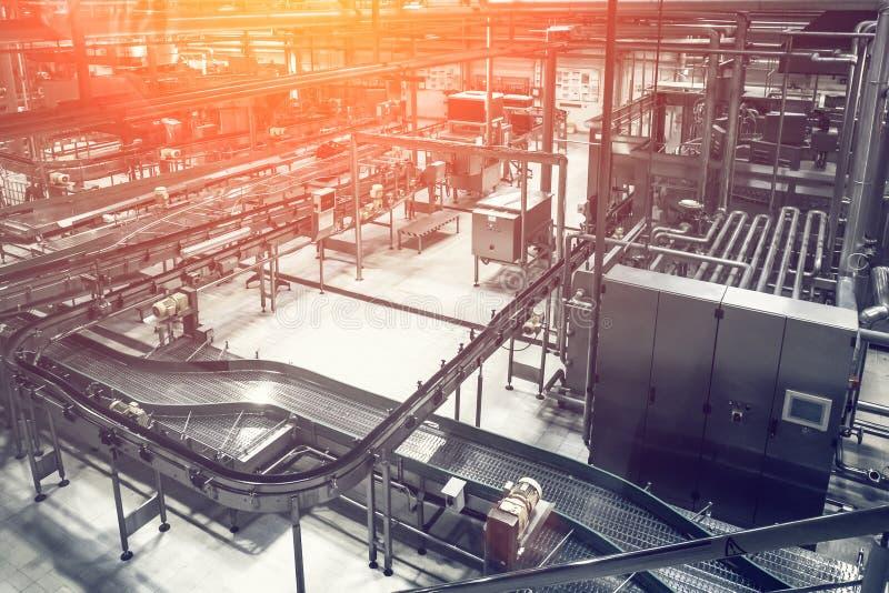 Línea moderna del transportador de la fábrica de la cervecería y muchas tuberías de acero, entonadas como fondo industrial abstra fotografía de archivo