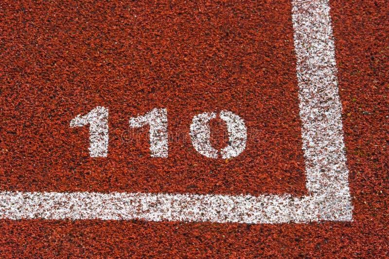 Línea roja estándar y número de goma 110 del color de la pista corriente y blanca imagen de archivo
