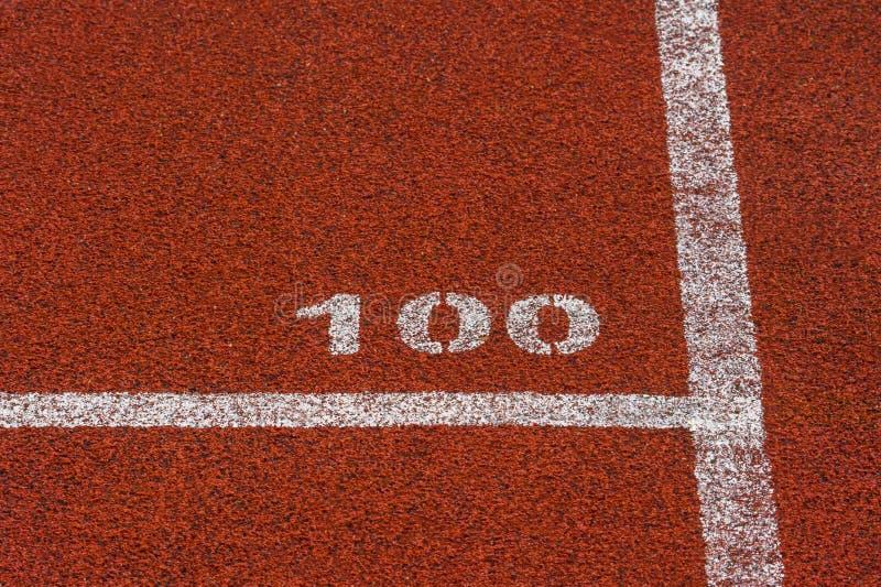 Línea roja estándar y número de goma 100 del color de la pista corriente y blanca fotografía de archivo libre de regalías