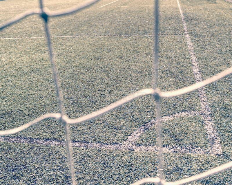 Líneas alrededor del campo de fútbol, lado de la esquina, hecho de césped sintético Visión detrás de la red fotografía de archivo libre de regalías