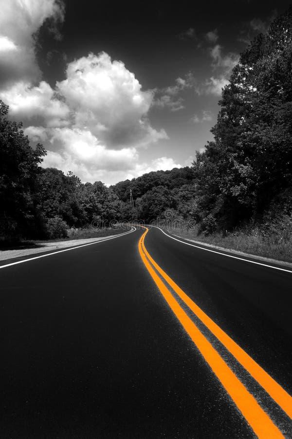 Líneas amarillas en un camino oscuro. imagen de archivo libre de regalías
