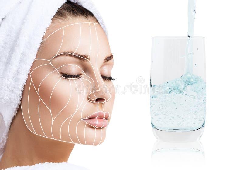 Líneas antienvejecedoras de la cirugía estética en cara y el vidrio femeninos con agua clara fotos de archivo