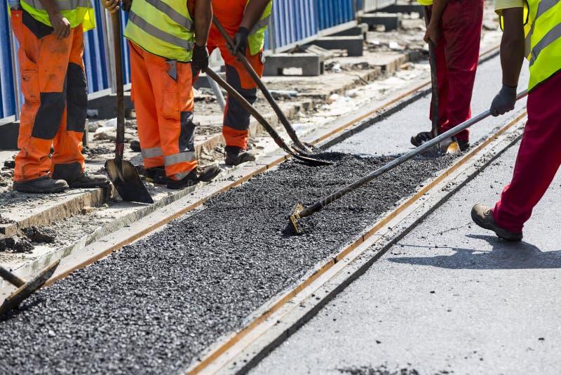 Líneas de la carretera y de ferrocarril de asfalto de la construcción de los trabajadores fotografía de archivo libre de regalías