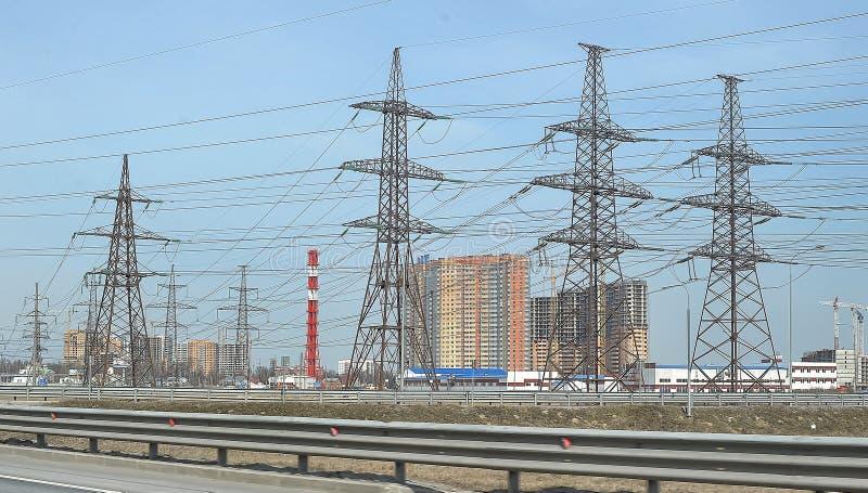 Líneas de transmisión de alto voltaje a lo largo del camino imagenes de archivo