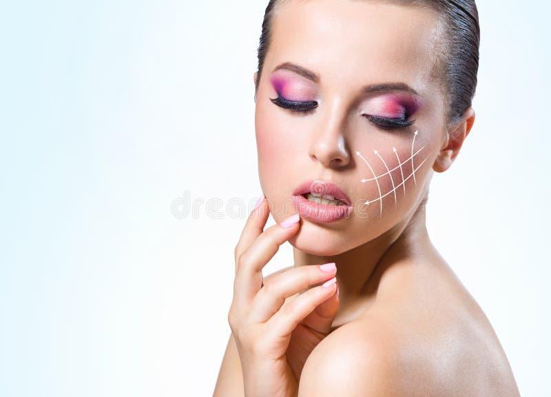 Líneas del masaje en la cara de la muchacha foto de archivo