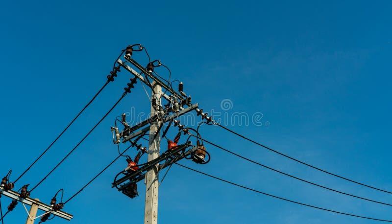 Líneas eléctricas de alto voltaje del polo y de transmisión con el cielo azul claro Pilones de la electricidad en campo de la ceb foto de archivo