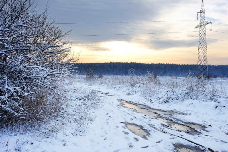 Líneas eléctricas de alto voltaje en la salida del sol en un invierno Mún camino fangoso del invierno Imagen hermosa del invierno fotos de archivo libres de regalías