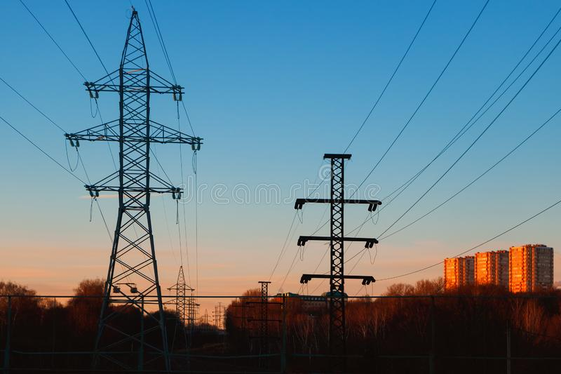 Líneas eléctricas de alto voltaje en un ambiente urbano en el fondo de la puesta del sol fotografía de archivo libre de regalías