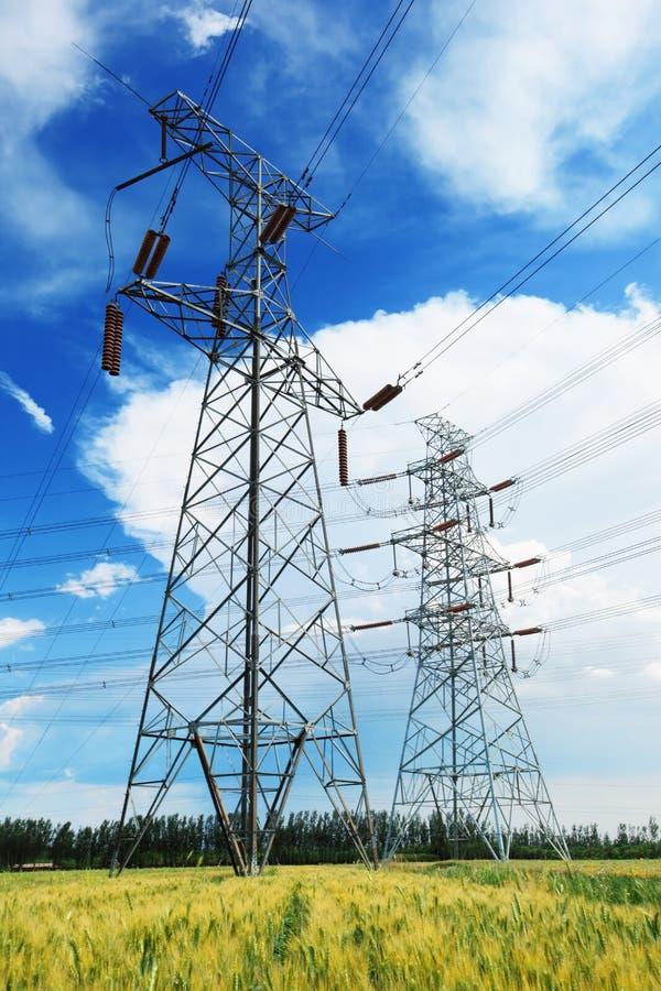 Líneas eléctricas de alto voltaje sobre campo de trigo imagenes de archivo