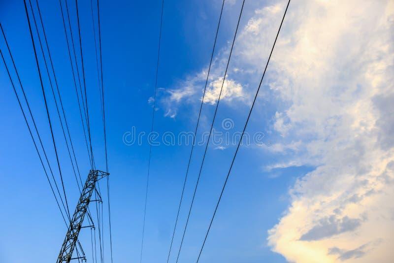 Líneas eléctricas de las torres de alto voltaje con las nubes y el cielo foto de archivo