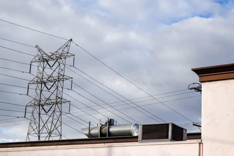 Líneas eléctricas de polos del metal al tejado constructivo contra un cielo nublado gris fotos de archivo libres de regalías
