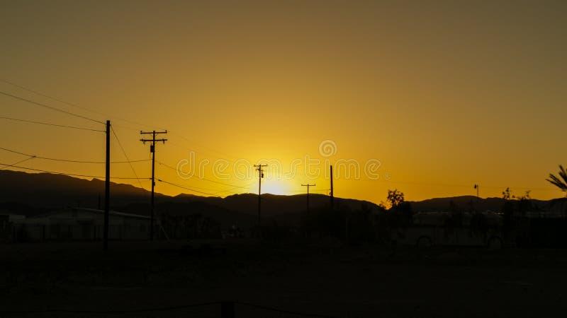 Líneas eléctricas en campo en fondo de la salida del sol Siluetas de polos con los alambres en el amanecer fotografía de archivo