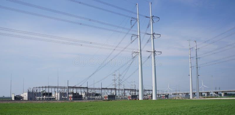 Líneas eléctricas y central eléctrica foto de archivo