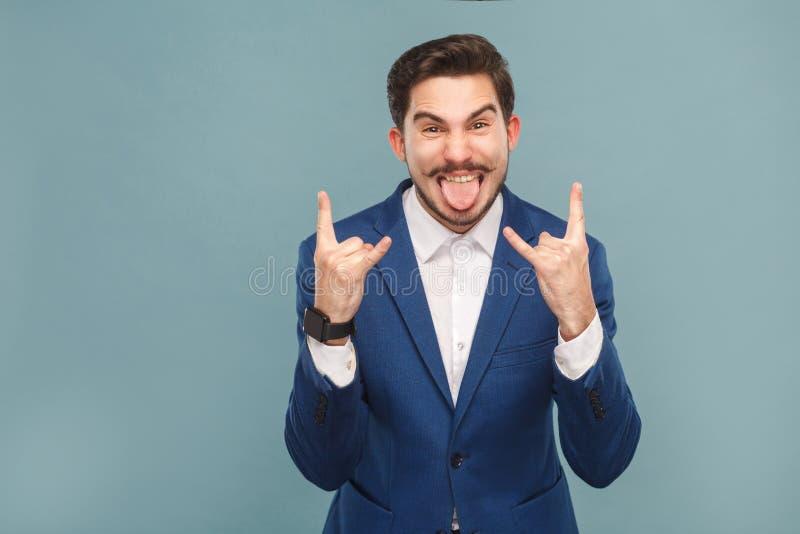 Língua agressiva do homem de negócios para fora e mostrando o sinal do rock and roll fotos de stock