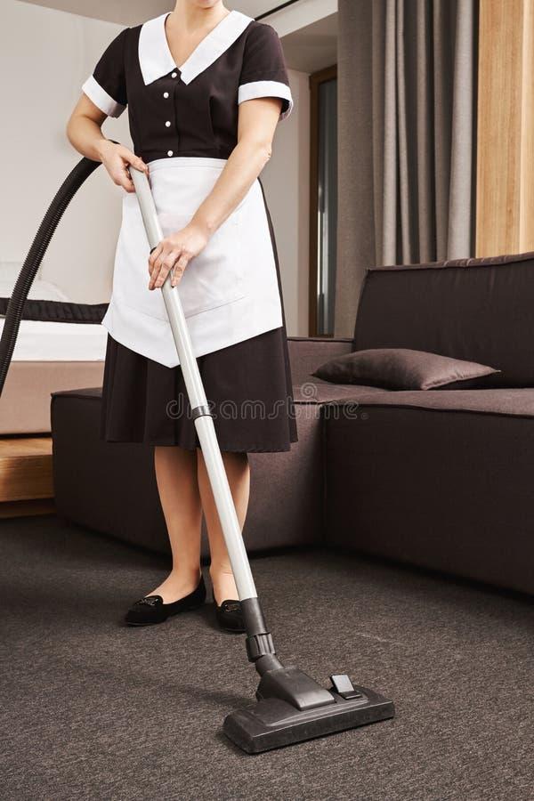 Lío del trapo apagado Tiro cosechado horizontal de la criada en la sala de estar uniforme de la limpieza del patrón con el aspira fotografía de archivo libre de regalías
