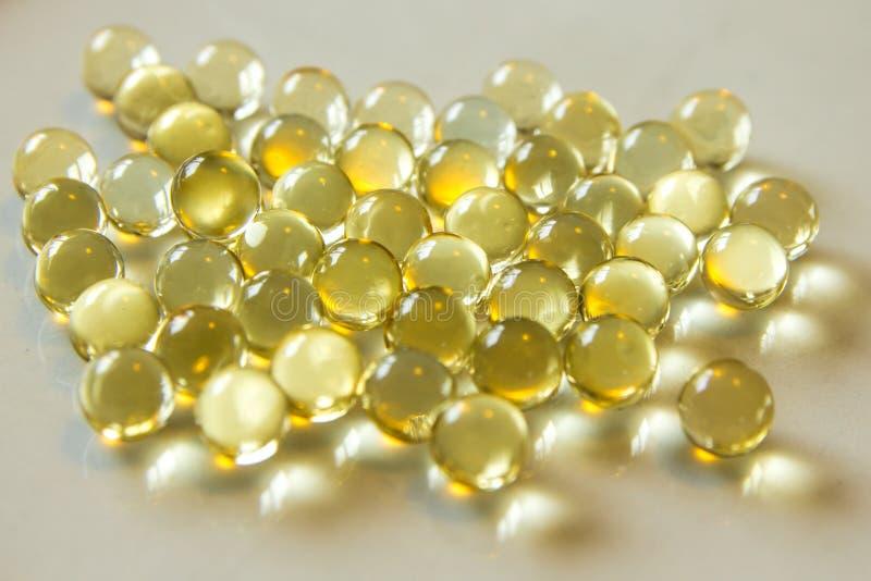 Líquido amarelo cápsulas enchidas dos comprimidos fotografia de stock