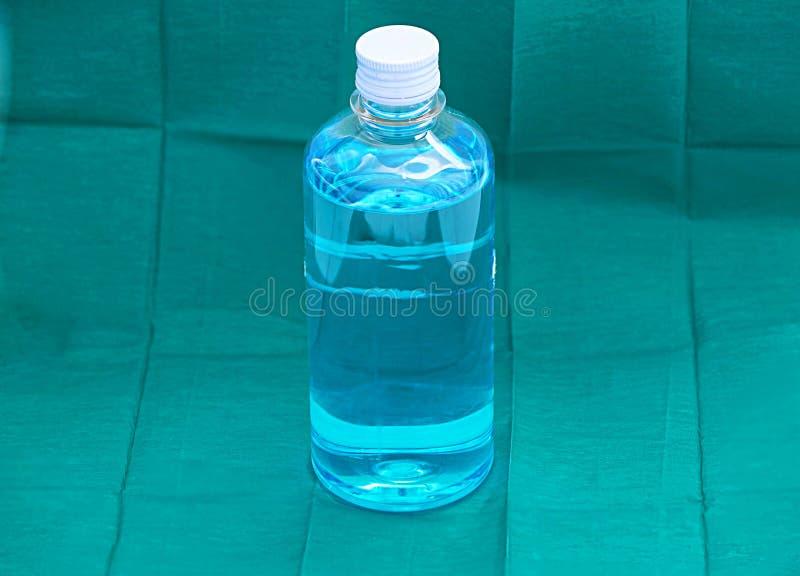 Líquido azul do álcool de etilo na garrafa transparente plástica no verde imagem de stock royalty free
