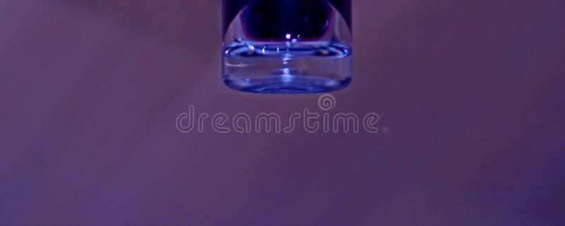 Líquido coloreado en la botella de cristal imagen de archivo