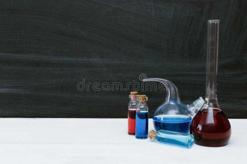 Líquido colorido em umas garrafas e em uns tubos de ensaio químicos Química biologia foto de stock royalty free