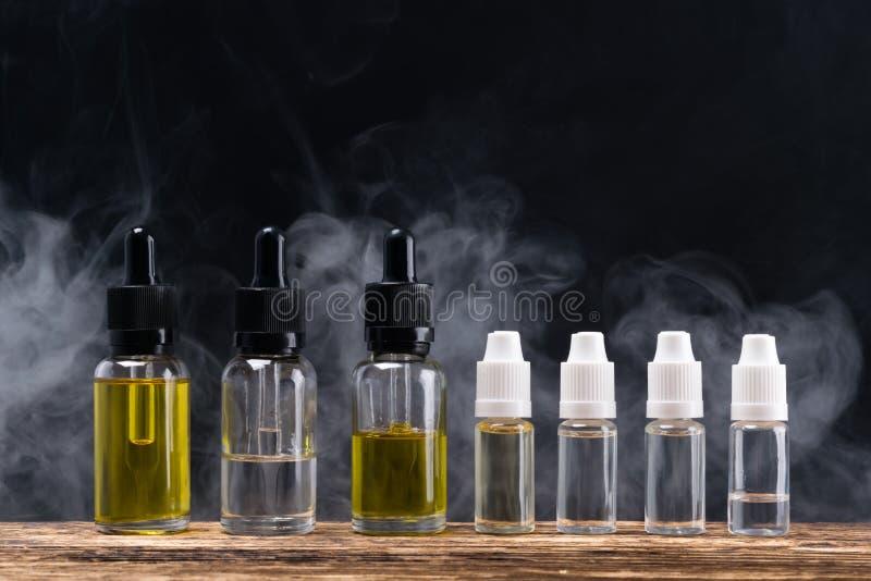 Líquido con los aromas sabrosos en las botellas para un cigarrillo electrónico, contra un fondo del vapor imágenes de archivo libres de regalías