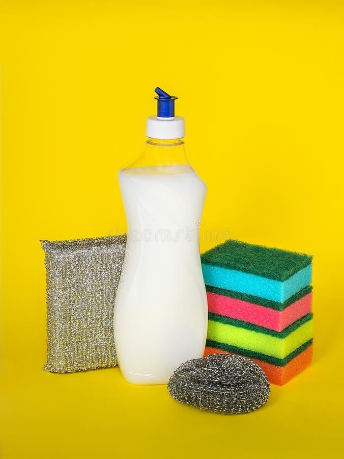 Líquido da lavagem da louça e três tipos de esponjas da dureza diferente em um fundo amarelo imagens de stock