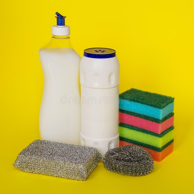 Líquido da lavagem da louça, pó e três tipos de esponjas da dureza diferente em um fundo amarelo imagens de stock