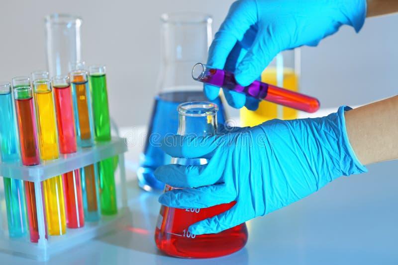 Líquido de colada del técnico de laboratorio del tubo de ensayo en el frasco en la tabla, primer imágenes de archivo libres de regalías