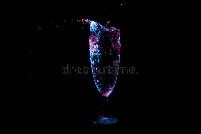 Líquido de colada en la flauta de champán en luz azul y roja en un fondo negro imagen de archivo libre de regalías