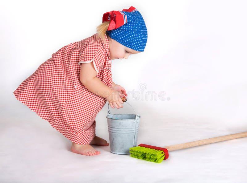 Líquido de limpeza da dona de casa da menina da criança imagens de stock
