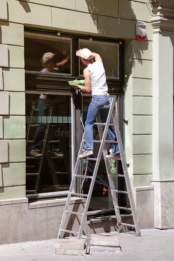 Líquido de limpeza de janela que trabalha em uma escada fotos de stock royalty free