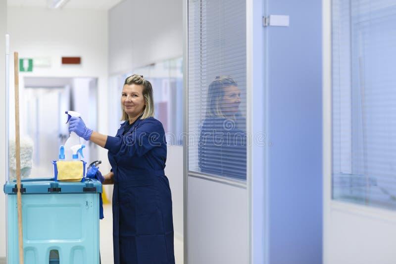Líquido de limpeza fêmea feliz que sorri no escritório imagens de stock royalty free