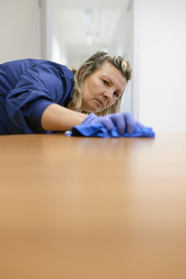 Líquido de limpeza fêmea profissional que limpa a tabela no escritório foto de stock