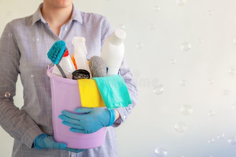Líquido de limpeza fêmea que guarda uma cubeta com fontes de limpeza imagens de stock royalty free
