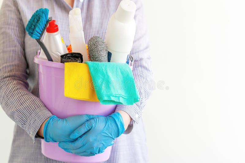 Líquido de limpeza fêmea que guarda uma cubeta com fontes de limpeza imagem de stock royalty free