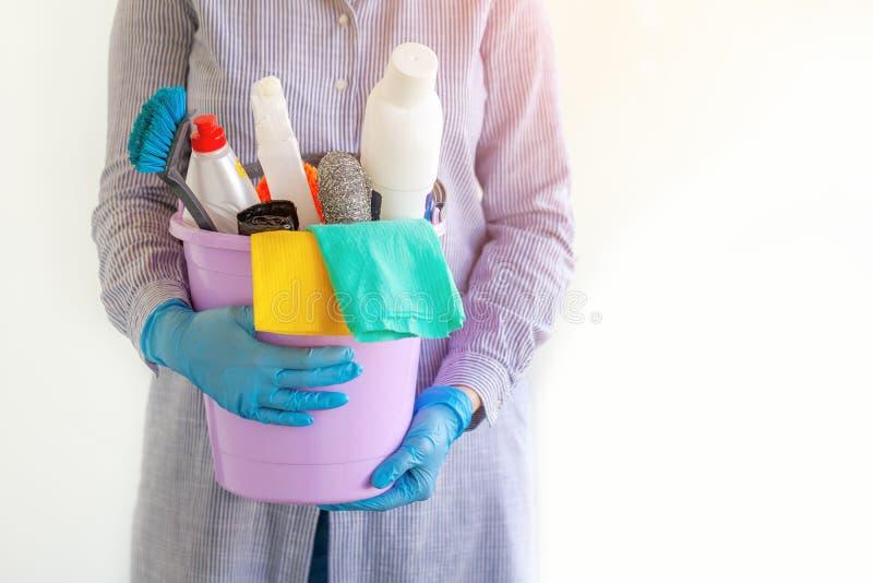 Líquido de limpeza fêmea que guarda uma cubeta com fontes de limpeza imagens de stock