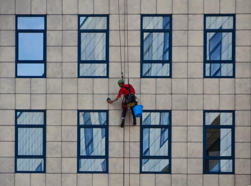 Líquido de limpeza de janela que trabalha na construção, limpando a fachada fotografia de stock royalty free