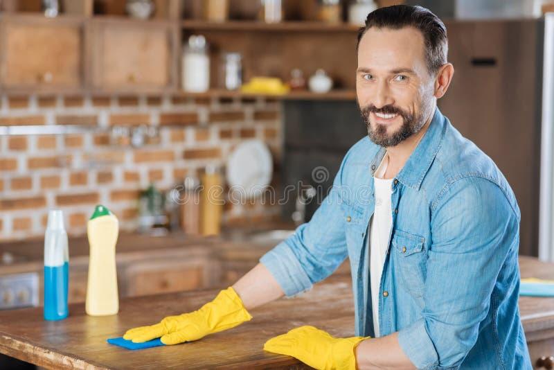 Líquido de limpeza masculino alegre que limpa a mesa foto de stock
